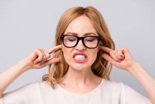 Angry pretty young woman in spectacles covering her ears with fingers and showing teeth